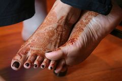 Mehndi decorated feet. Mehndi artists decorated feet of the bride with Henna designs for Indian Muslim Wedding preparation royalty free stock photo