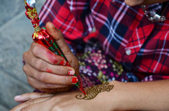 Mehndi or Henna india style at Nepal. Mehndi or Henna is a paste that is bought in a cone shaped tube and is made into designs for men and women. It is also stock images