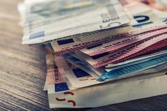 Mehrere Hundert Eurobanknoten gestapelt durch Wert Eurogeldkonzept Euroanmerkungen mit Reflexion Fokus auf Seil Fünf, 10 und fünf Lizenzfreie Stockfotos