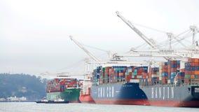 Mehrfache Frachtschiffe, die am Hafen von Oakland laden Stockbilder