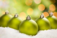 Mehrfache grüne Weihnachtsverzierungen auf Schnee über einem abstrakten Hintergrund Stockfoto