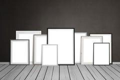 Mehrfache leere Bilderrahmen, die auf Wand sich lehnen Lizenzfreie Stockfotos