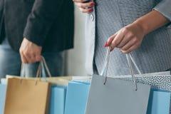 Mehrfache Taschenhände der Einkaufsjahreszeitverkaufsmannfrau stockfoto