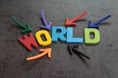 Mehrfacher Pfeil, der auf die hölzernen Alphabete aufbauen das Wort WELT in der Mitte der Zementtafelwand, wichtig von der Welt z lizenzfreie stockfotos