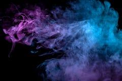 Mehrfarben-, dicker Rauch, belichtet, durch gefärbt im blauen, purpurroten und rosa Licht gegen einen dunklen schwarzen lokalisie stockfotos