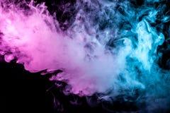 Mehrfarben-, dicker Rauch, belichtet, durch gefärbt im blauen, purpurroten und rosa Licht gegen einen dunklen schwarzen lokalisie stockfotografie