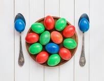 Mehrfarben-Ostereier auf hölzernem Teller Lizenzfreie Stockfotos