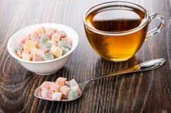 Mehrfarben-rakhat-lukum im Löffel, Schüssel mit rakhat-lukum, Tasse Tee auf Tabelle lizenzfreie stockfotos