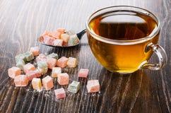 Mehrfarben-rakhat-lukum im Löffel und auf Tabelle, Tasse Tee zerstreut auf Tabelle stockbild