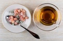 Mehrfarben-rakhat-lukum, Löffel in der Untertasse, Tasse Tee auf Untertasse auf Tabelle Beschneidungspfad eingeschlossen lizenzfreies stockfoto