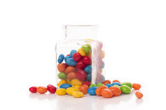 Mehrfarbensüßigkeiten auf einem weißen Hintergrund, der aus einem Glas heraus fällt Stockbilder
