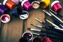 Mehrfarbige Acrylfarben und Kunstbürsten auf einem Holztisch Stockfotos