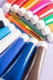 Mehrfarbige Acrylfarbenrohre stellten mit fünf bunten Bürsten ein Stockfotografie