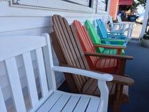 Mehrfarbige Adirondack-Stühle auf einem Portal Lizenzfreie Stockbilder