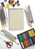Mehrfarbige Aquarellfarben, -bleistifte, -PASTELLE und -bürsten auf einem weißen Hintergrund Stockbild