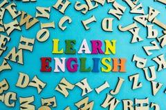 Mehrfarbige Aufschrift 'lernen Englisch 'auf einem blauen Hintergrund, zerstreute Buchstaben lizenzfreie stockbilder