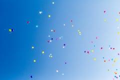 Mehrfarbige Ballone im blauen Himmel an einem sonnigen Tag Lizenzfreie Stockfotos