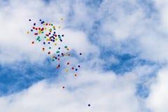 Mehrfarbige Ballons, die in einen bewölkten blauen Himmel schwimmen Stockfoto