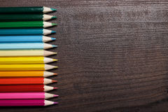 Mehrfarbige Bleistifte auf der braunen hölzernen Tabelle Lizenzfreie Stockfotos
