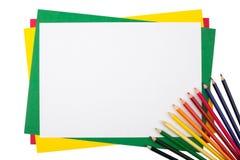 Mehrfarbige Bleistifte auf einem Rahmen von farbigem Papier Lizenzfreie Stockfotografie