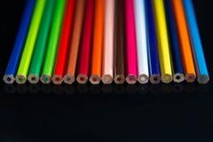 Mehrfarbige Bleistifte auf einem schwarzen Hintergrund stockfotos