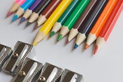 Mehrfarbige Bleistifte befinden sich gegenüber von den Bleistiftspitzern Kreatives Konzept lizenzfreies stockbild