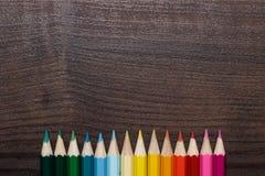 Mehrfarbige Bleistifte über brauner hölzerner Tabelle Stockfotografie
