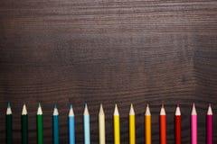Mehrfarbige Bleistifte über brauner hölzerner Tabelle Stockfotos