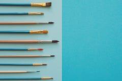 Mehrfarbige Bleistifte und Bürsten auf dem blauen Papier Zurück zu Schule Lizenzfreie Stockbilder