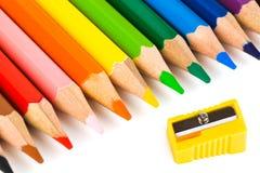 Mehrfarbige Bleistifte und Bleistiftspitzer Stockbilder