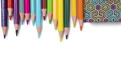 Mehrfarbige Bleistifte und Buch auf weißem Hintergrund Stockfotografie