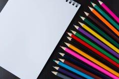 Mehrfarbige Bleistifte und ein Papiernotizblock Lizenzfreie Stockfotografie