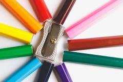 Mehrfarbige Bleistifte und silberner Bleistiftspitzer Pinsel und Rolle Lizenzfreie Stockfotos