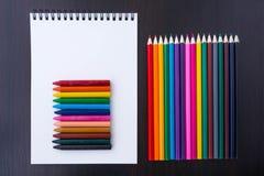 Mehrfarbige Bleistifte, Zeichenstifte und ein Papiernotizblock Stockfoto