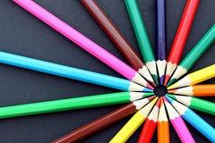 Mehrfarbige Bleistiftlüge ganz herum auf einem schwarzen Hintergrund Lizenzfreie Stockfotografie