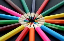Mehrfarbige Bleistiftlüge ganz herum auf einem schwarzen Hintergrund Stockfotografie