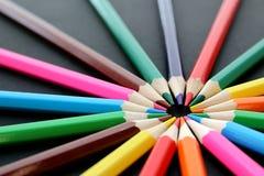Mehrfarbige Bleistiftlüge ganz herum auf einem schwarzen Hintergrund Stockbild