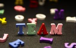 Mehrfarbige Buchstaben des Teams auf Schwarzem Stockfoto