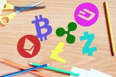 Mehrfarbige cryptocurrency Symbole liegen auf einem hölzernen Schreibtisch Stockfotografie