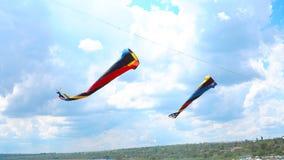 Mehrfarbige Drachen, die gegen den blauen Himmel und die Wolken fliegen Stockbild