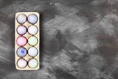 Mehrfarbige Eier für Ostern im Behälter für Eier auf schwarzem BAC Lizenzfreie Stockfotos