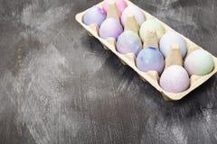 Mehrfarbige Eier für Ostern im Behälter für Eier auf schwarzem BAC Lizenzfreies Stockbild