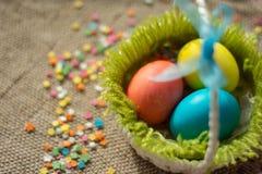 Mehrfarbige Eier in festlichem Korb Ostern auf Segeltuchserviette lizenzfreies stockfoto