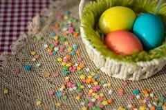 Mehrfarbige Eier in festlichem Korb Ostern auf Segeltuchserviette lizenzfreie stockfotos
