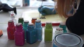Mehrfarbige Flaschen Farbe M?dchenk?nstler zeichnet Buchstaben auf dem Farbbrett stock footage