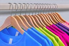 Mehrfarbige Frauen ` s T-Shirts hängen an den hölzernen Aufhängern lizenzfreie stockfotos