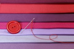 Mehrfarbige Gewebeproben Knopf mit einer Nadel und einem Thread an stockfoto