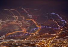 Mehrfarbige glühende Linien auf einem dunklen Hintergrund stockfotografie