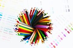 Mehrfarbige hölzerne Bleistifte und Farbpalette Lizenzfreie Stockfotos