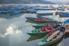 mehrfarbige hölzerne Boote auf dem See gegen den Hintergrund von grünen Bergen blaue rote grüne gelbe leere Boote auf dem Wasser lizenzfreie stockfotos
